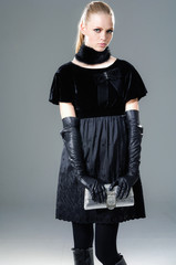fashion model in gloves holding little purse posing