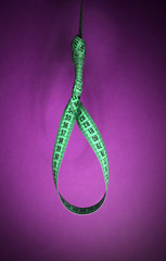 Tape measure noose on purple background - diet concept