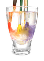Brushes with color paint in glass of water, isolated on white