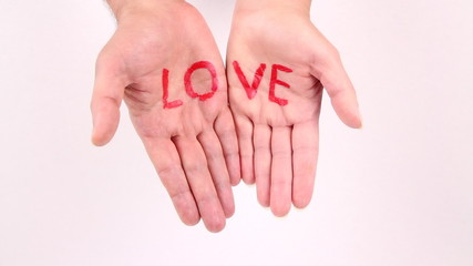 Male and female hands gather and show word love