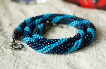 Knitted necklace from blue beads of two shades