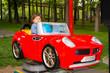 Toddler boy having fun in a car in park