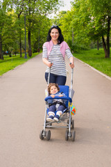 Happy mom pushing pram with toddler in park