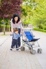 Mother and toddler boy pushing pram