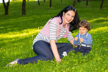 Cheerful mother and boy sit in grass
