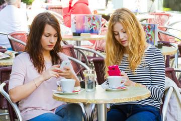 Zwei junge Frauen mit Handy im Cafe