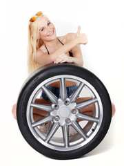 Sexy woman with summer tire shows thumb up