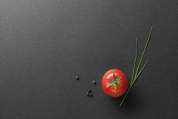 red tomato with green onion on black. top view