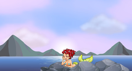 A young mermaid near the rocks at the seaside