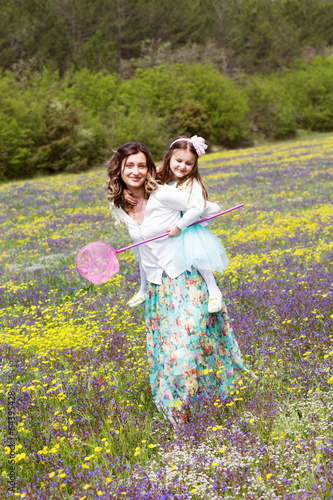Mother and daughter in field with colorful flowers