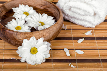 Spa decoration with daisies floating in wooden bowl