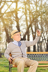 An old man taking a selfie seated on bench outdoors