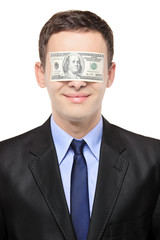 Businessman with a dollar bill blinding his eyes