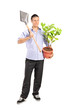 Man holding a shovel and a plant