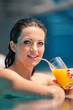 Young woman portrait relaxing and having a drink in a swimming p
