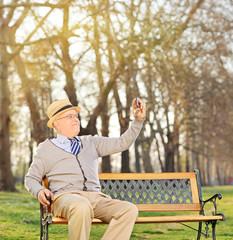 Senior adult taking a selfie in park