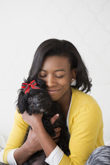 A young girl cuddling her small black pet dog.