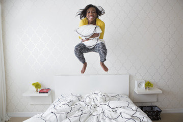 A young girl jumping high in the air above her bed.