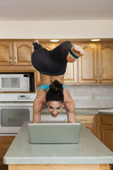 A woman doing a handstand balancing on a kitchen top and checking her laptop.