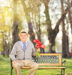Senior man posing in park with red tulips