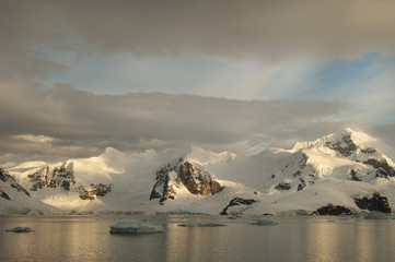 Dusk and flat calm water off the shore of a mountain landscape in Antarctica.
