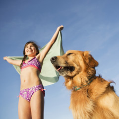 A girl in a beach towel with a golden retriever dog.