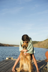 A girl in a swimming towel, cuddling a golden retriever dog.