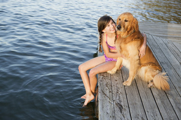 A girl and her golden retriever dog seated on a jetty by a lake.