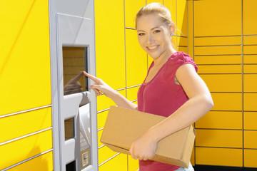 Frau bringt Päckchen zur Paket-Station