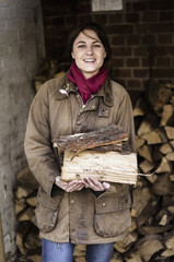 A woman carrying split logs for firewood from a large log store.