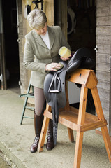 A woman cleaning and preparing tack and saddle, in the courtyard of a riding stable.