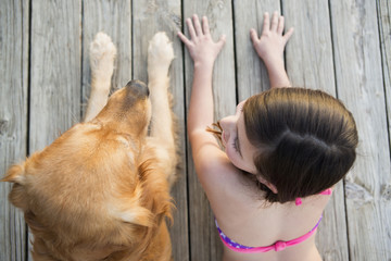 A young girl and a golden retriever dog side by side on a jetty.