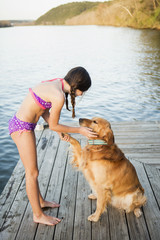 A girl in a bikini with a golden retriever dog lifting its paw up.