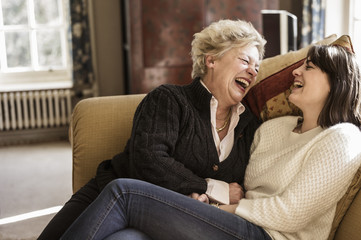 Two women, mother and daughter, sitting side by side, laughing.