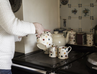 A woman pouring tea, by a range cooker. Using decorative china.