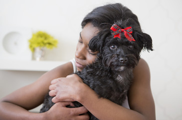 A young girl hugging her small black pet dog.