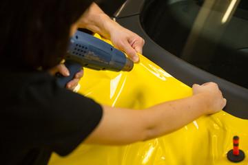 Car wrappers using heat gun to prepare vinyl foil
