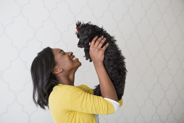A young girl holding her small black pet dog.