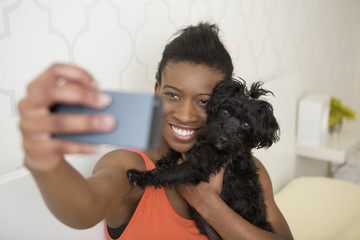 A young girl taking a selfy of her small pet dog and herself.