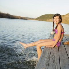A girl in a bikini sitting on a jetty with her feet in the water.