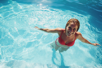 Girl standing in a swimming pool smiling