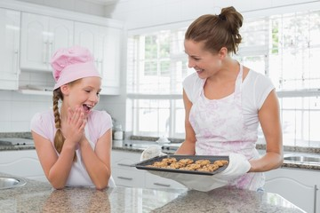 Smiling woman and girl with freshly prepared cookies in kitchen
