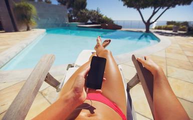Woman sunbathing on deckchair with phone
