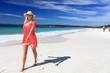 Happy woman walking along beautiful beach