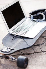 Laptop and headphones on skateboard