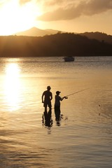 father and son family fishing at sunset