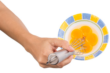 Female hand whisking egg yolk in ceramic bowl