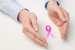 Female Hands Protecting Pink Ribbon