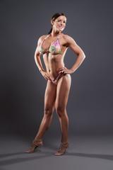 Muscled fitness woman wearing bikini. Brown hair. Studio shot ag