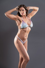 Muscled fitness woman wearing bikini. Brown hair with flower. St